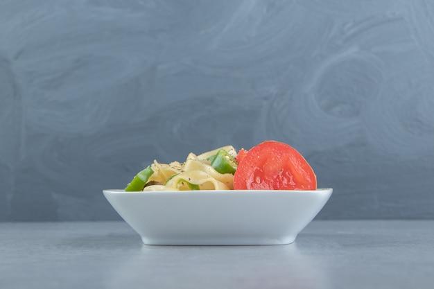 Вкусный феттуцин с овощами в белой миске.