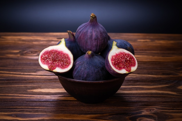 Tasty figs in a bowl on wooden