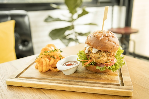 Tasty fired chicken with arugula and mayonnaise sauce served on wooden board, fired chicken cheese burger with spicy seasoned curly fries