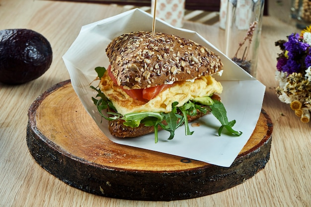 Tasty fitnes burger from rye buns with salmon, omelet, arugula and cucumbers on a wooden board on a wooden table. fishburger. healthy snack. close up view