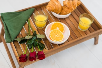 Tasty food and flowers on breakfast table