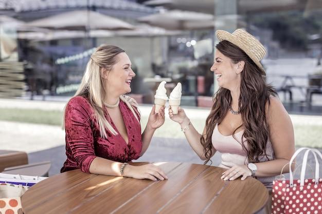Вкусная еда. радостные счастливые женщины аплодируют мороженым, сидя вместе в кафе