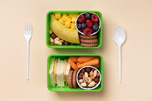 Disposizione di scatole per il pranzo di cibo gustoso piatto disteso