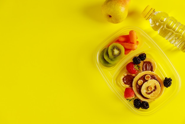 Tasty food in lunch boxes on yellow surface