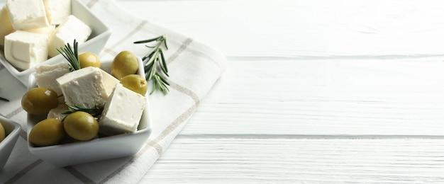 Вкусная еда с сыром фета на белой деревянной поверхности