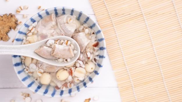 おいしいフォートニックスハーブフレーバースープ、ハーブを使った台湾の伝統料理、白い木製のテーブルに豚の腸、クローズアップ、フラットレイ、上面図。