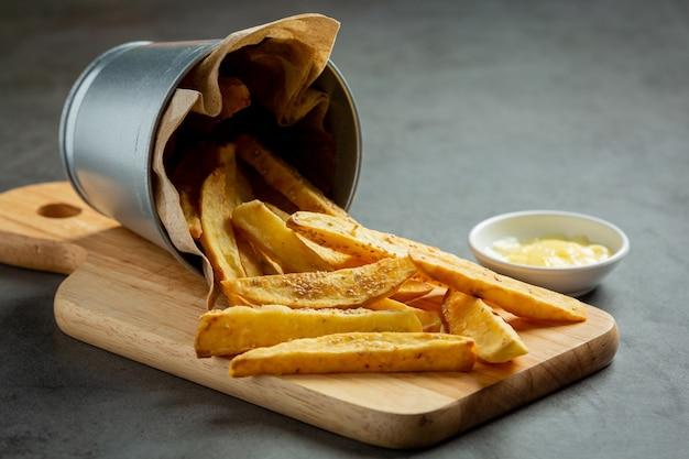Tasty french fries on on dark background