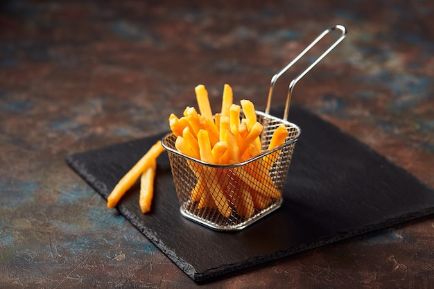 Tasty french fries in iron basket on slate cutting board