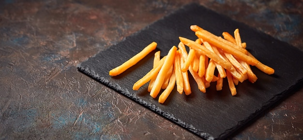 Tasty french fries on slate cutting board, on dark background