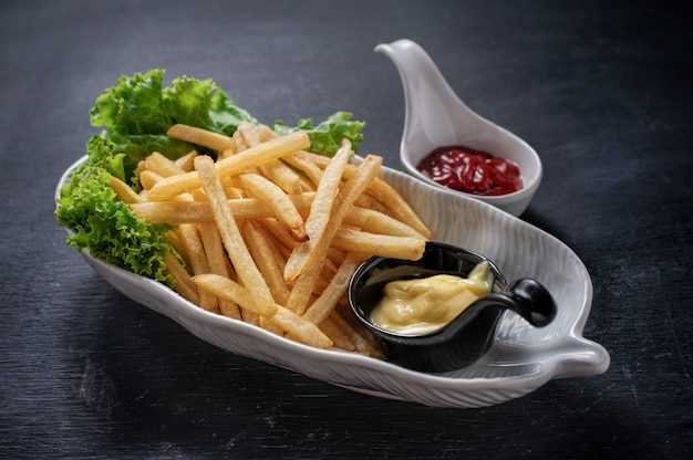 Tasty french fries on white plate, on wooden table