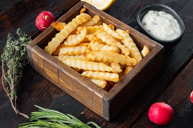 Tasty french fries with herbs set in wooden box on old dark  wooden table background