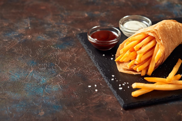 Tasty french fries with sauces on slate cutting board, on dark background