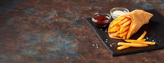 Tasty french fries with sauces on slate cutting board