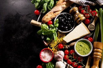 Tasty fresh appetizing italian food ingredients on dark background.