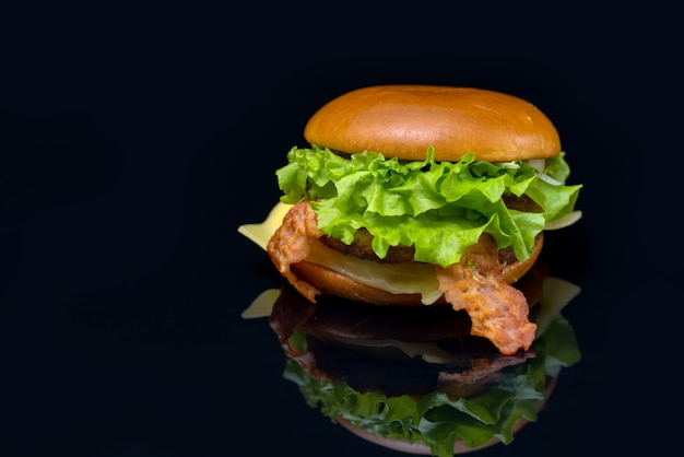 Tasty fresh bacon cheeseburger on a reflective black surface with copy space suitable for menu advertising