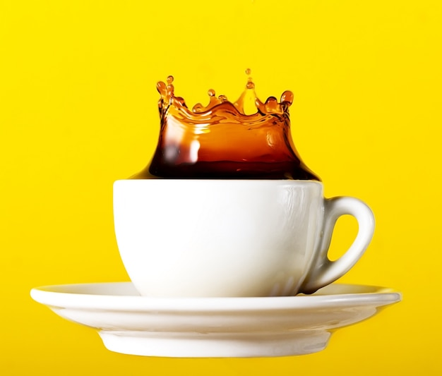 Tasty fresh black coffee in cup splash crown on yellow vibrant background. art design