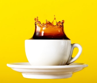 Tasty fresh black coffee in cup splash crown on yellow vibrant background. Art Design