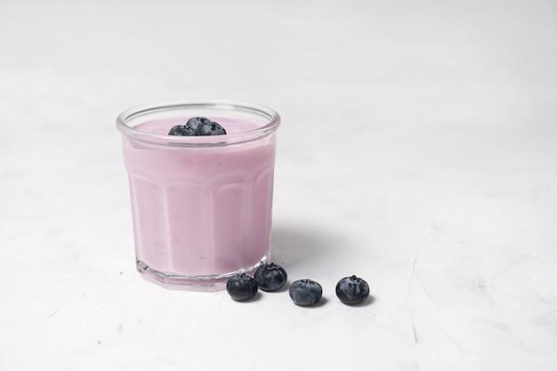 Tasty fresh blueberry yoghurt shake dessert in glass standing on white table . homemade berry smoothie. healthy eating. diet food yogurt