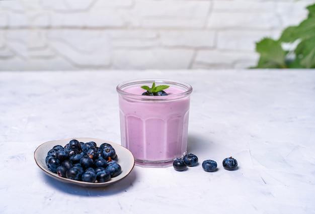 おいしい新鮮なブルーベリーヨーグルトは、白いテーブル背景にガラス立ってでデザートを振る。自家製ベリーのスムージー。健康的な食事。ダイエットフードヨーグルト