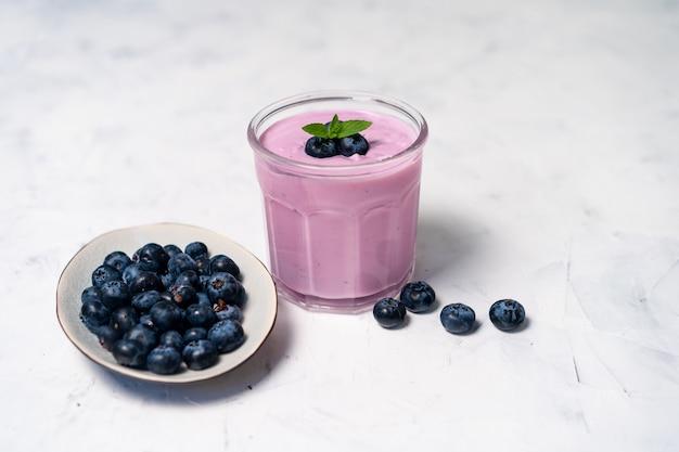 白いテーブルの背景の上に立っているガラスのおいしい新鮮なブルーベリーヨーグルトシェイクデザート。自家製ベリーのスムージー。健康的な食事。ダイエットフードヨーグルト