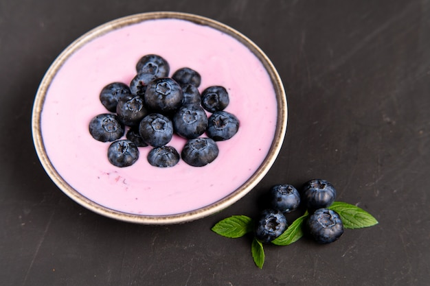 おいしい新鮮なブルーベリーヨーグルトは、黒いテーブル背景にセラミックボウル立ってでデザートを振る。自家製ベリーのスムージー。健康的な食事。ダイエット食品。