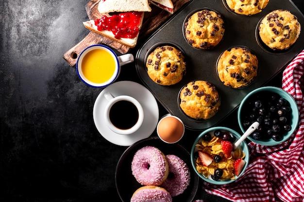 Вкусные свежие ингредиенты ингредиентов для завтрака на черном темном фоне. готовы готовить. главная концепция здорового питания.