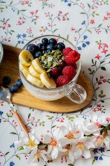 木製のテーブルの上のベッドでおいしい新鮮な朝食。フルーツ入りヨーグルト。ヴィンテージホワイトインテリア