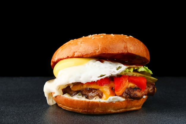 Вкусный свежий бургер с яйцом на темном фоне изолированные. домашний гамбургер со свежими овощами и сыром крупным планом