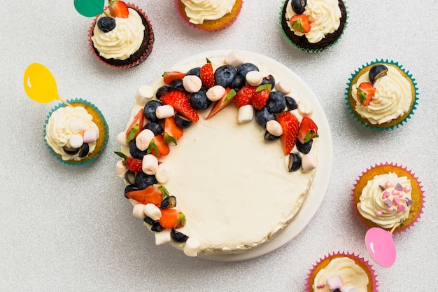 Tasty fresh cake with berries and set of little muffins on table