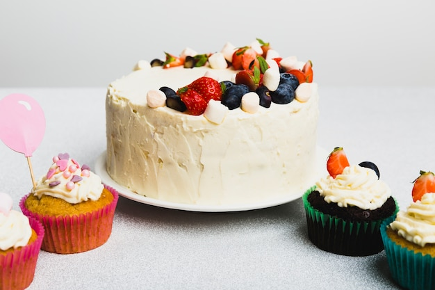 Tasty fresh cake with berries and set of little muffins
