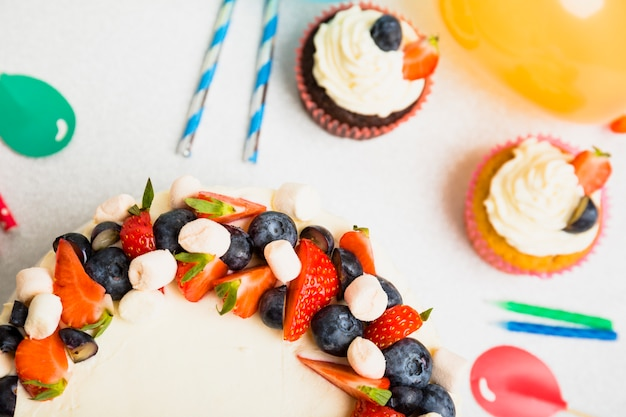 Tasty fresh cake with berries on table near ornament balloons