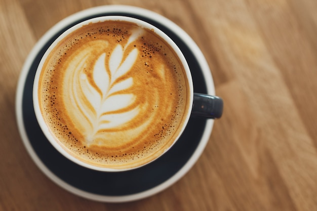 Tasty fresh cappuccino in cup on wooden table. closeup