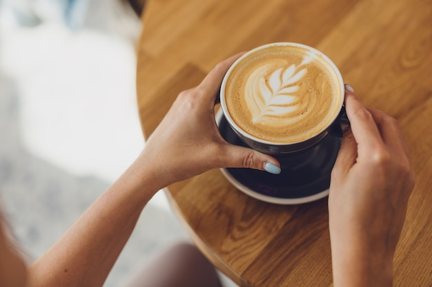 Tasty fresh cappuccino in cup on wooden table. unrecognizable woman holding cup in hands.