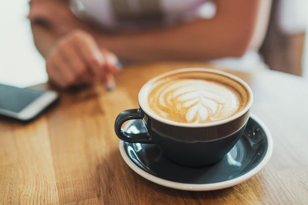 木製のテーブルの上のカップでおいしい新鮮なカプチーノ。背景に認識できないビジネスウーマン