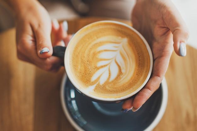 木製のテーブルの上のカップでおいしい新鮮なカプチーノ。手にカップを持っている認識できない女性。