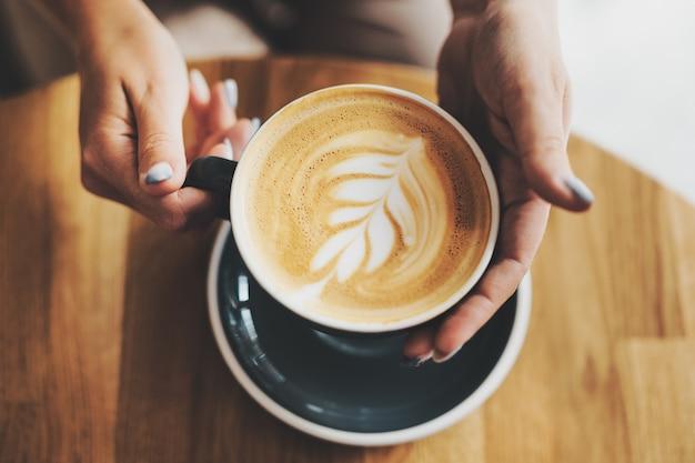 Вкусный свежий капучино в чашке на деревянном столе. до неузнаваемости женщина, держащая чашку в руках.