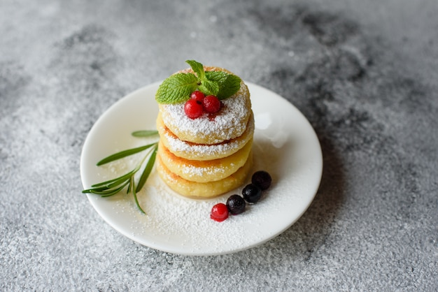 Tasty fresh cottage cheese pancakes on a white plate on a concrete background. healthy and diet breakfast