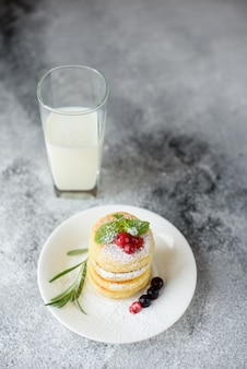 Tasty fresh cottage cheese pancakes on a white plate with a glass of milk on a concrete background. healthy and diet breakfast
