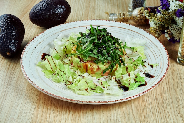 Tasty, fresh green salad with salmon, lettuce, avocado, parmesan on a white plate on a wooden table. healthy diet