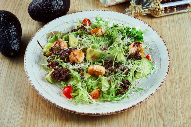 Tasty, fresh green salad with shrimp, lettuce, avocado, parmesan and cherry tomatoes on a white plate on a wooden table. healthy nutrition. close up on food.