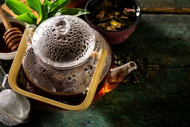 Вкусный свежий зеленый чай в стеклянной чайной церемонии на старом деревенском столе