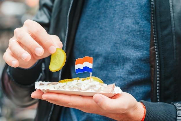 암스테르담 트라드의 수로 배경에 양파와 네덜란드 국기가 달린 맛있는 신선한 청어...