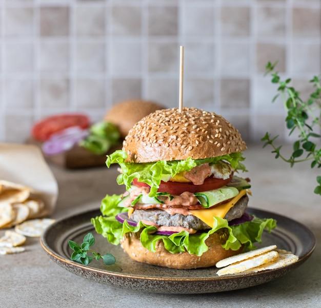 ファーストフードやジャンクフードを作るための材料を使ったセラミックプレート上のおいしい新鮮な自家製ビーフバーガー