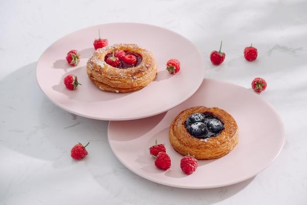 흰색 나무 테이블에 딸기와 맛있는 신선한 홈 메이드 퍼프 페이스 트리 프리미엄 사진