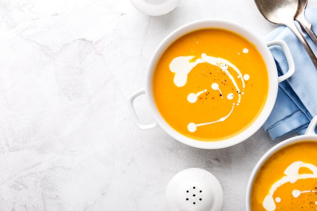 Tasty fresh pumpkin creamy soup with cream on grey marble background.