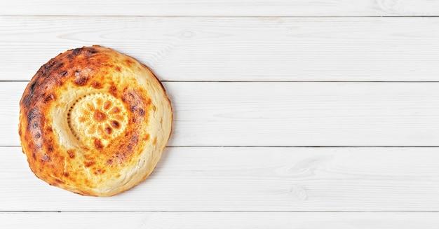 Вкусный свежий круглый хлеб тандыр на белой деревянной поверхности