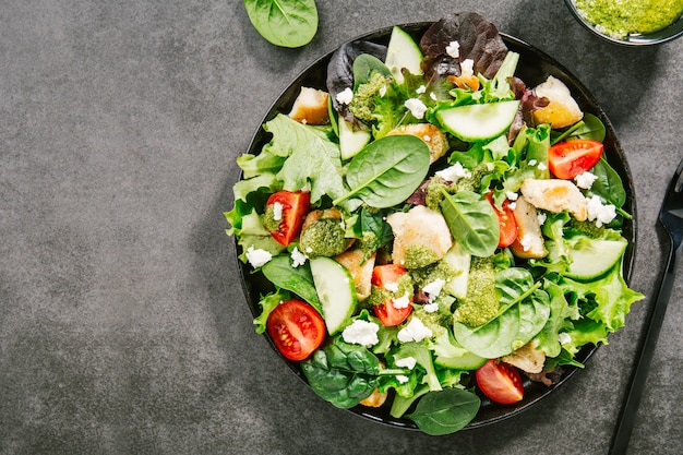 Tasty fresh salad with chicken, pesto and vegetables
