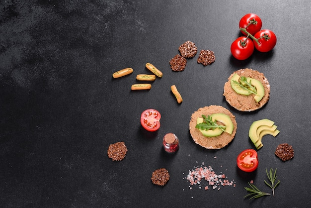 Tasty fresh sandwich with liver paste, avocado pieces and a arugula on a dark concrete table