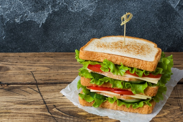 Tasty and fresh sandwiches on a dark wooden table.