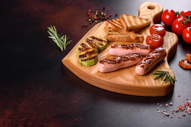 野菜のスパイスとハーブで焼いた、おいしい新鮮なソーセージ。暗いコンクリートのテーブルの上に完成した料理の写真
